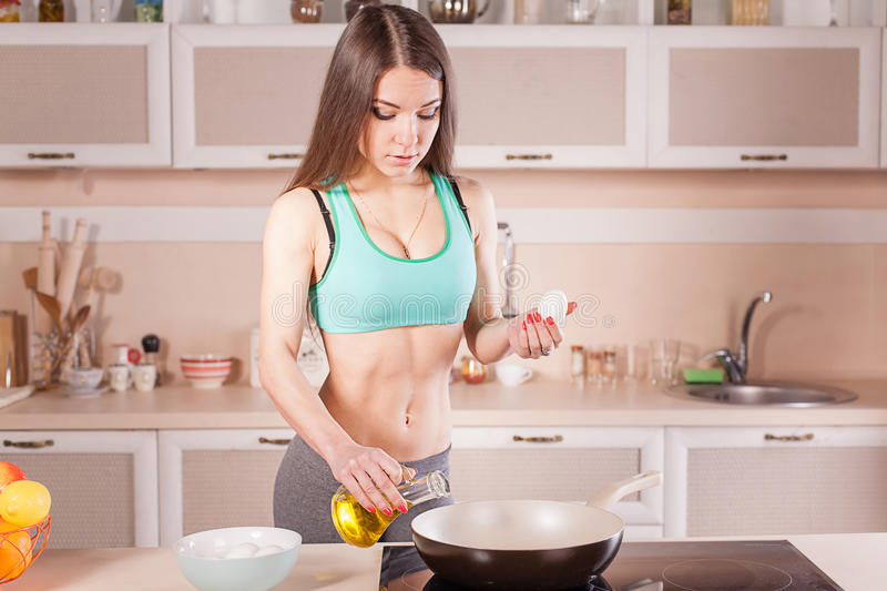 Fitness girl cooking healthy food. At the kitchen royalty free stock photo