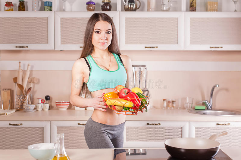 Fitness girl cooking healthy food. At the kitchen stock image