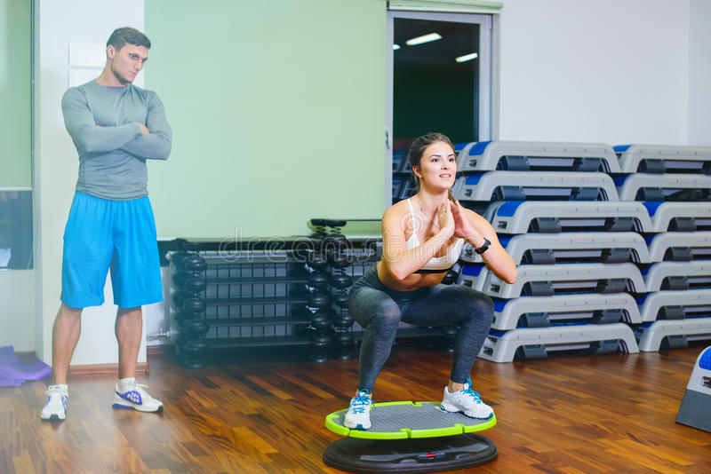The fitness girl on the core platform coach. The fitness girl on the core platform with the coach crouches, concept health, sports stock images