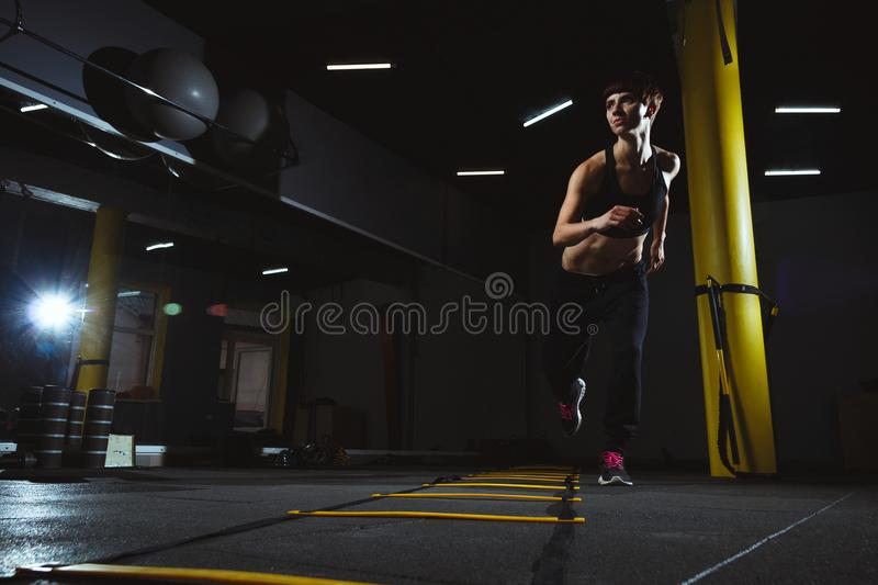 Fitness girl doing crossfit exercises in gym in dark hall, sport stock photos