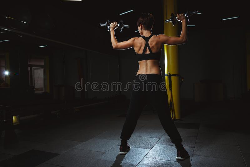 Fitness girl doing crossfit exercises in gym with dumbels in dar stock photography