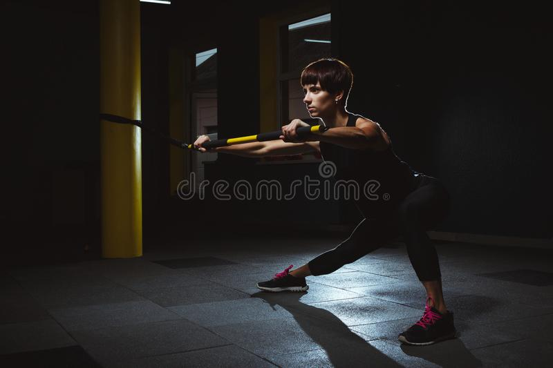 Fitness girl doing crossfit exercises in gym with trx in dark ha royalty free stock image