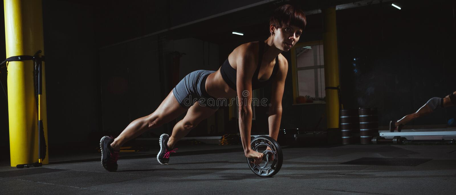 Fitness girl doing crossfit exercises in gym with wheel in dark royalty free stock photos