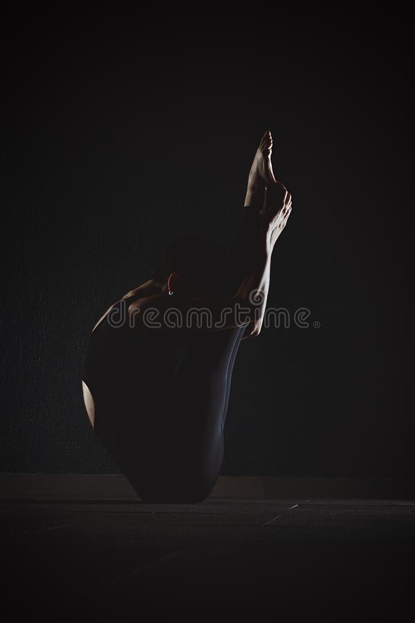 Fitness girl doing crossfit exercises in gym yoga pose in dark h royalty free stock photo