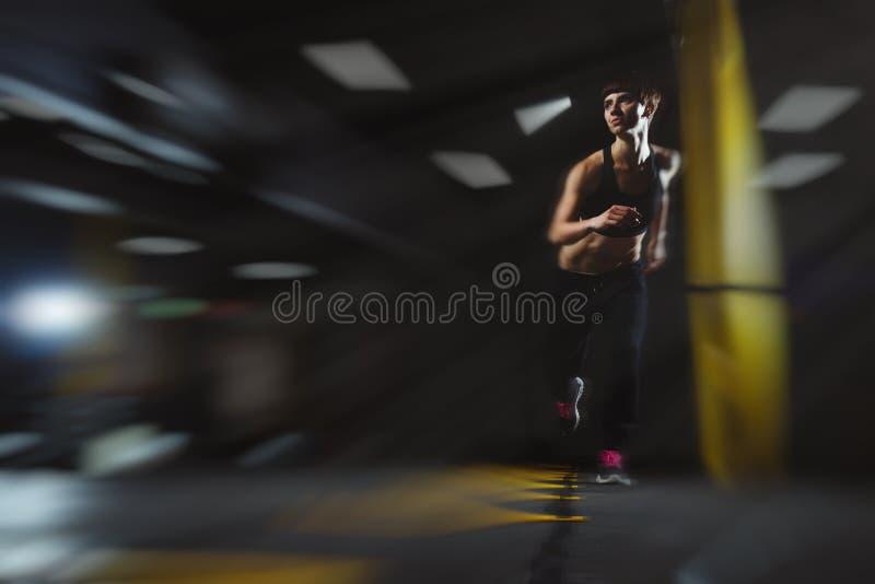 Fitness girl doing exercises in gym in dark hall, sporty woman s. Fitness girl doing exercises in gym in dark hall, sporty woman in pose doing functional stock images