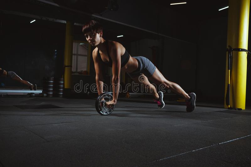 Fitness girl doing exercises in gym with wheel in dark hall, sporty woman in pose doing functional training, poster banner h. Ealthy lifestyle royalty free stock photo