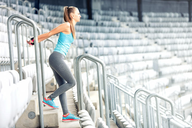Fitness girl doing fitness exercises and working out on stadium stairs. Jogger on morning training, healthy lifestyle concept stock photo