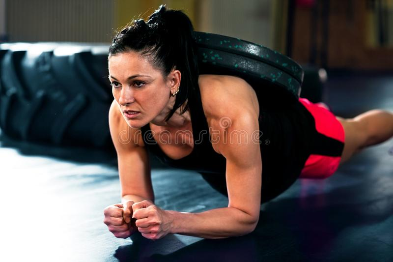 Fitness girl doing hard exercises in gym. Strong Fitness girl doing hard intensive exercises in dark gym stock images