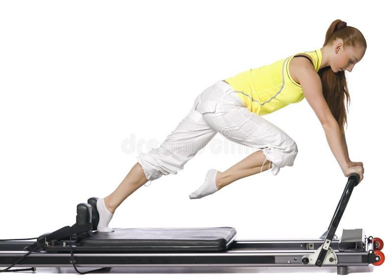 Fitness girl doing pilates on the allegro stock images