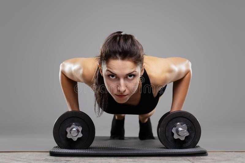 Fitness girl doing push ups. With weights stock images
