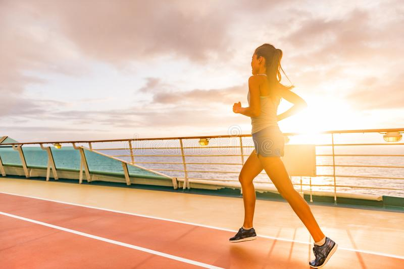 Fitness girl doing running cardio workout on cruise vacation. Fit woman jogging at sunset on run lanes on deck of cruise ship. During summer holidays. Active royalty free stock photos