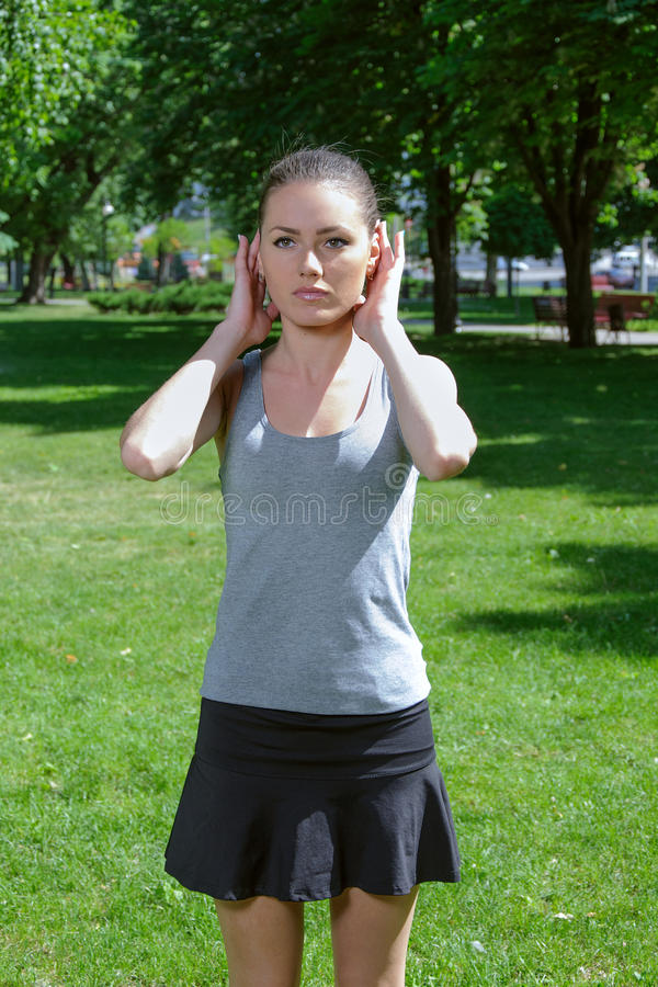 Fitness girl doing self-massage of the neck while standing on th stock photo