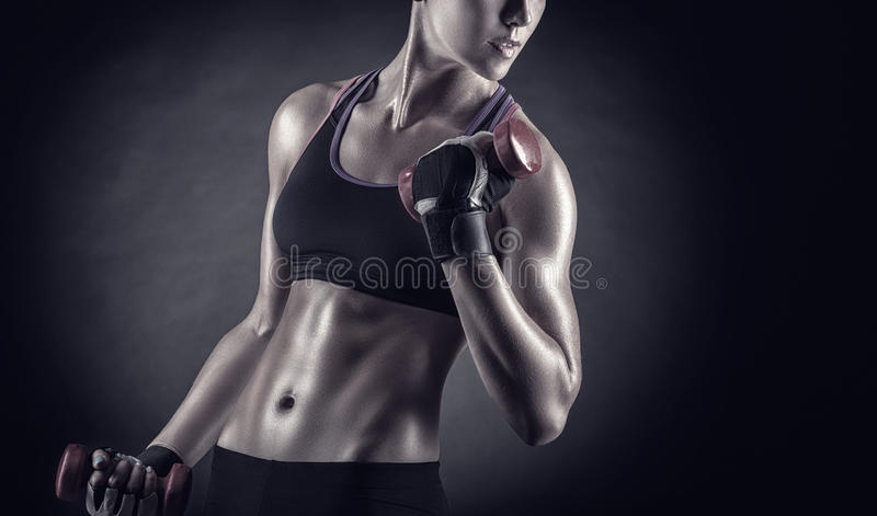 Fitness. Girl with dumbbells on a dark background