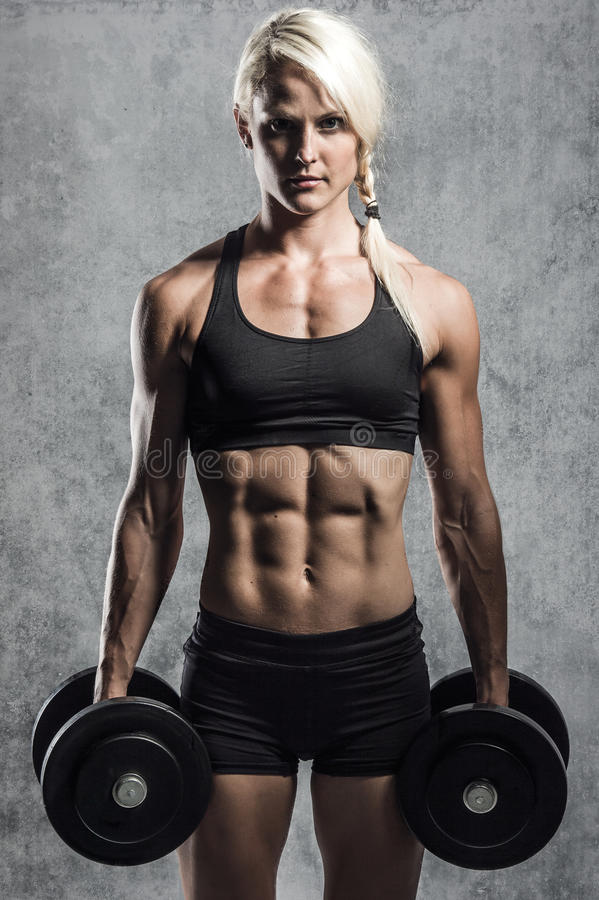 Fitness girl with dumbells. A young and very fit woman training with dumbells royalty free stock images