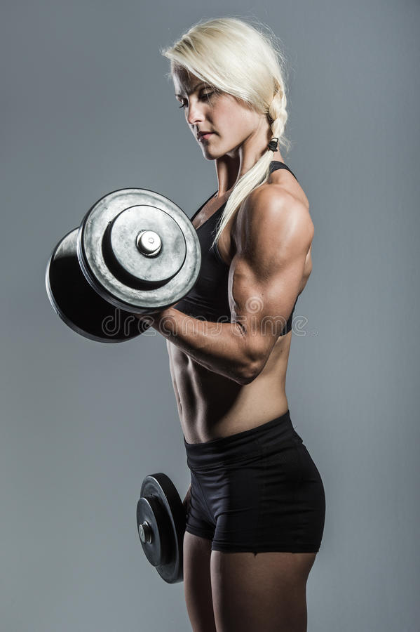 Fitness girl with dumbells. A young and very fit woman training with dumbells stock photo