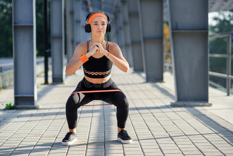 Fitness girl with earphones which doing squat exercises with fabric booty band during her sport workout on special. Fitness girl in earphones which doing squat stock images