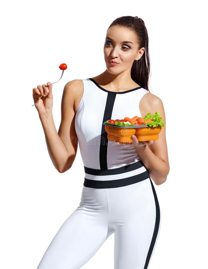 Fitness girl enjoying healthy food. Photo of latin girl in fashionable sportswear isolated on white background. Healthy nutrition stock photography