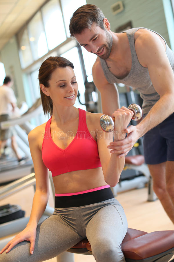 Fitness girl excercising with her coach stock photography