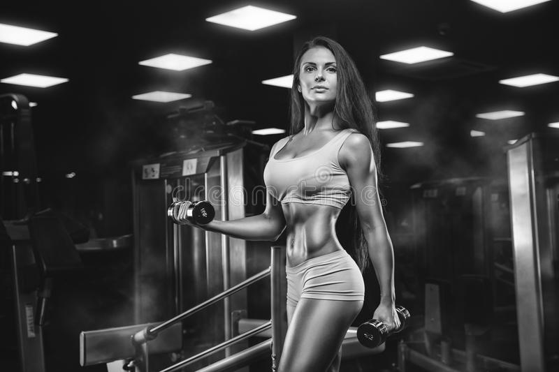 Fitness girl exercising with barbell in gym. Brutal athletic woman pumping up muscles stock photography