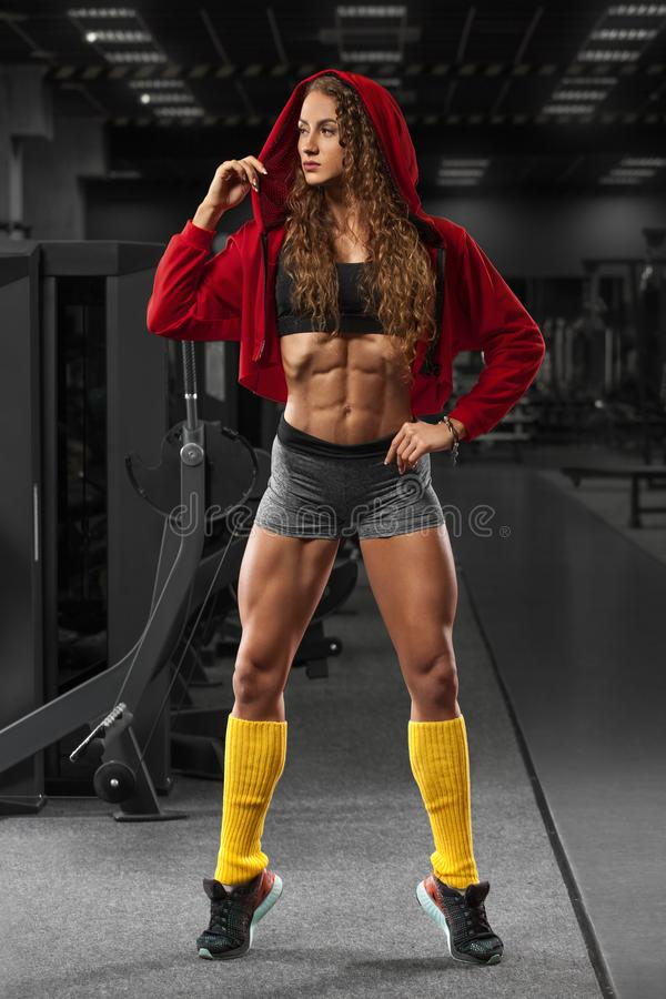Fitness girl in gym, flat belly, abs. Beautiful muscular woman, shaped abdominal.  royalty free stock photos