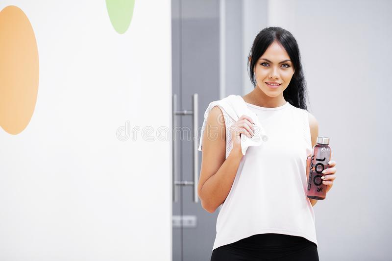 Fitness girl. Happy young woman holding a towel and bottle water stock images