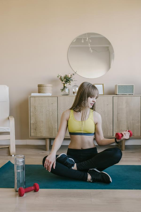 Fitness girl in at home raises the bar up at the floor. She wears yellow sporing t-shirt stock photography
