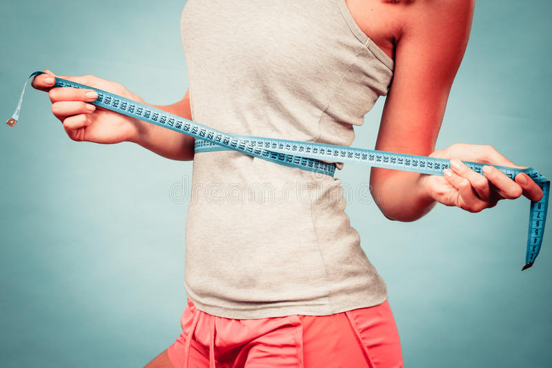 Fitness girl measuring her waistline. Weight loss, slim body, healthy lifestyle concept. Fit fitness girl measuring her waistline with measure tape on blue stock photo