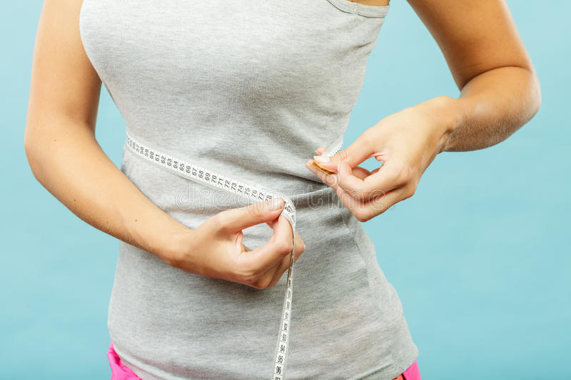 Fitness girl measuring her waistline. Weight loss, slim body, healthy lifestyle concept. Fit fitness girl measuring her waistline with measure tape on blue stock photos