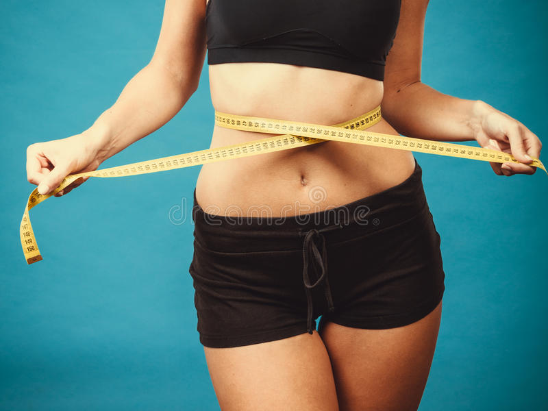 Fitness girl measuring her waistline. Weight loss, slim body, healthy lifestyle concept. Fit fitness girl measuring her waistline with measure tape on blue royalty free stock photos