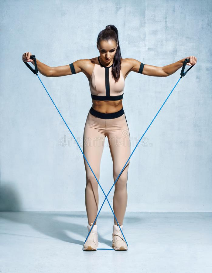 Fitness girl performs exercises with resistance band. Photo of fitness model workout on grey background. Strength and motivation stock photography