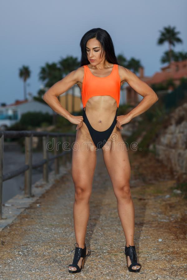 Fitness girl posing with a beautiful black and orange bikini royalty free stock photo