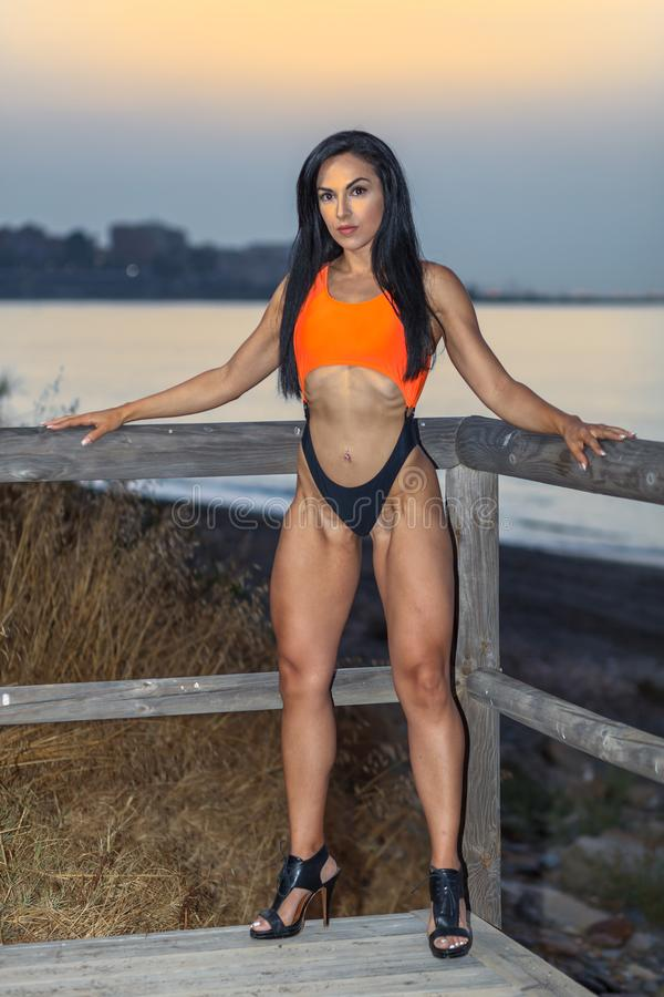 Fitness girl posing with a beautiful black and orange bikini royalty free stock photography