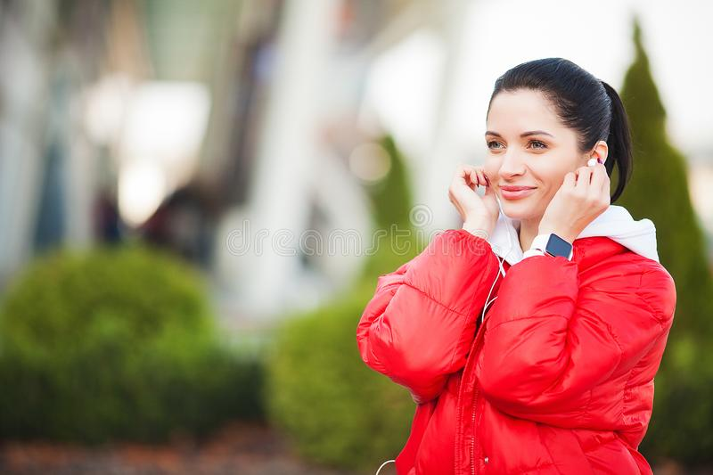 Fitness girl. Pretty sporty girl running and listening music outdoor. Healthy lifestyle in the big city royalty free stock image