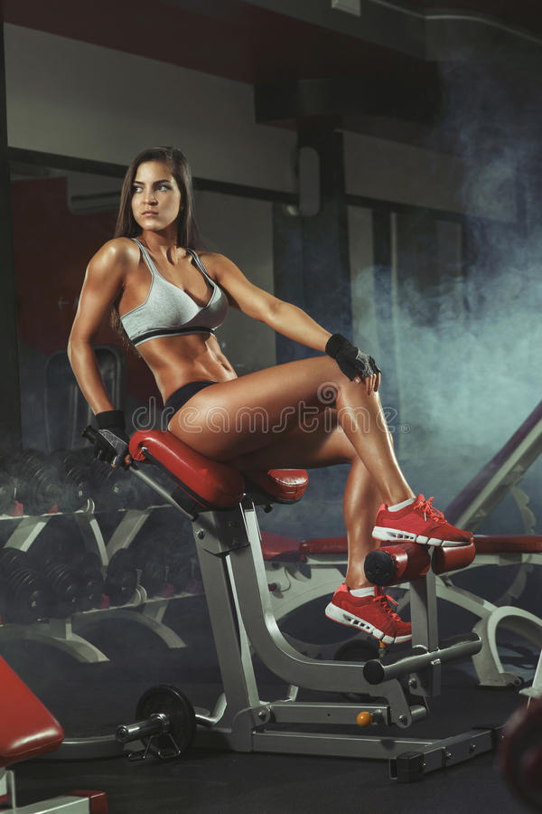 Fitness girl resting after lifting barbell royalty free stock photography