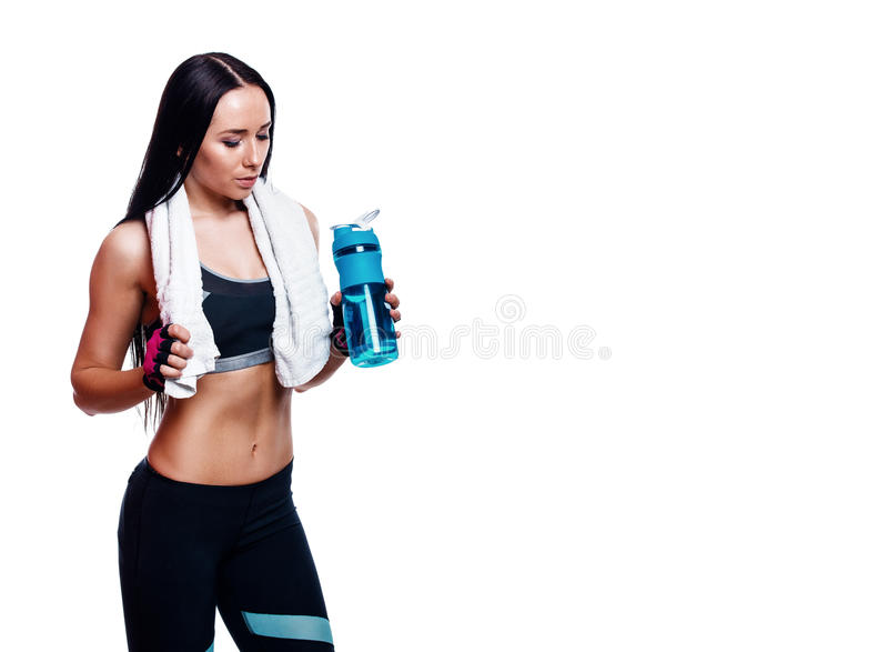 Fitness girl with shaker and towel on a white background. Attractive athletic woman relaxing after workout. Fitness girl with shaker and towel on a white stock photos