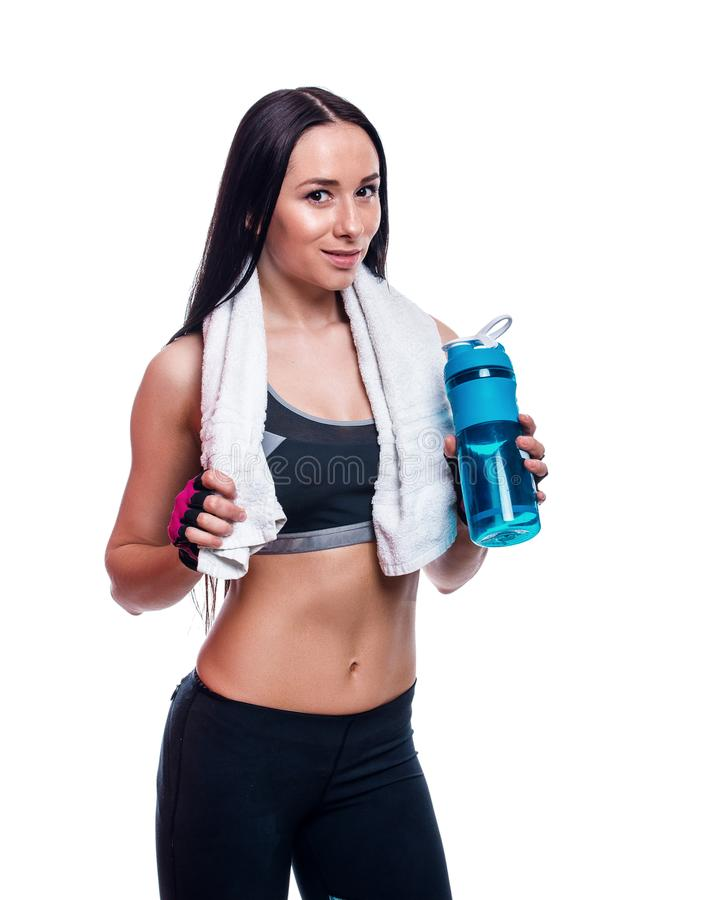 Fitness girl with shaker and towel on a white background. Attractive athletic woman relaxing after workout. stock image
