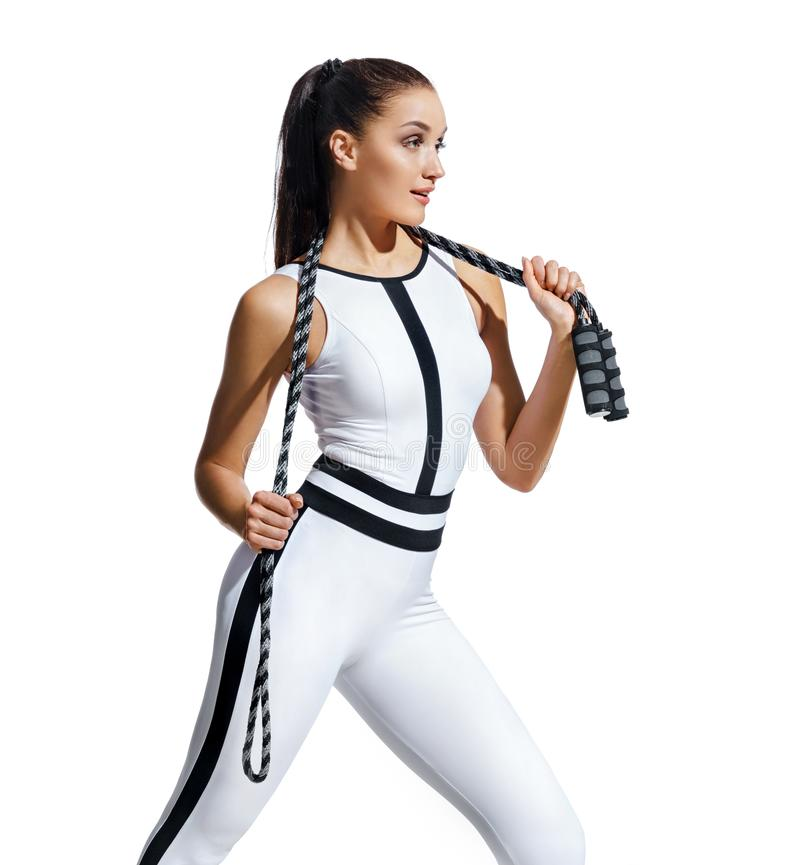 Fitness girl with skipping rope after exercising. Photo of latin girl in white sportswear isolated on white background. Best cardio workout royalty free stock image