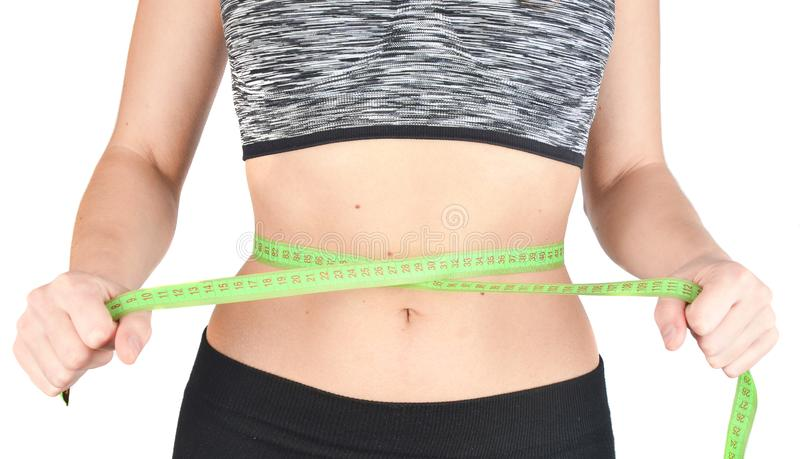 Fitness girl in sports tops measuring ruler waist on white background. The concept of losing weight stock image