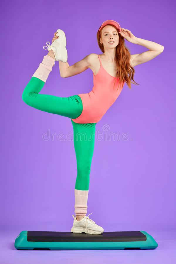 View of flexible girl standing on one leg at step deck, doing stretching exercises royalty free stock photography