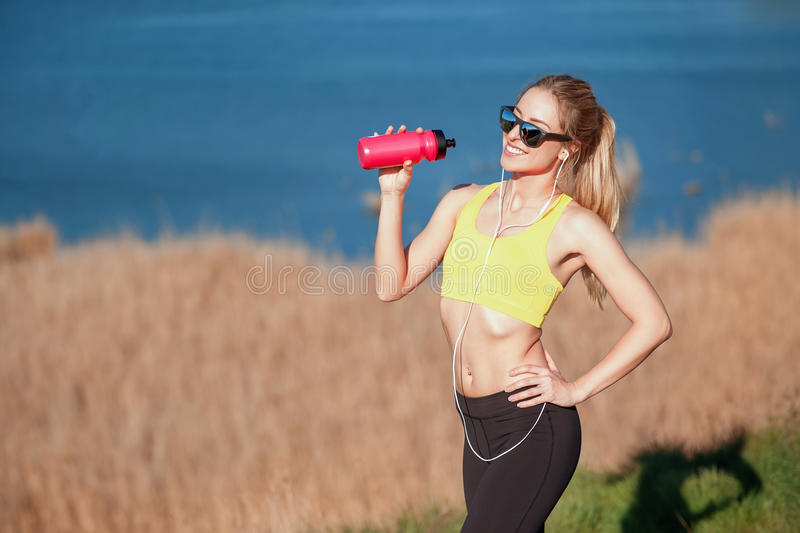 Fitness girl stopped to drink water after the running. sport and work out girl in sunny day stock photos