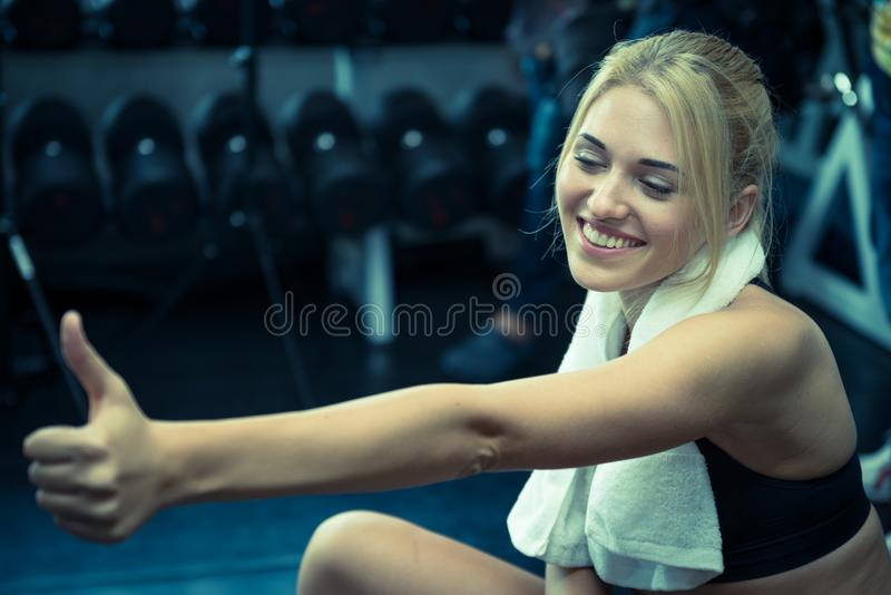 The fitness girl thumbs up and smile after exercise royalty free stock image