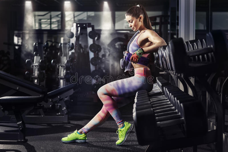 Fitness girl with towel and shaker relaxing in the gym royalty free stock image