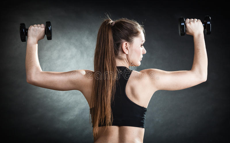 Fitness girl training shoulder muscles lifting dumbbells back view stock photography