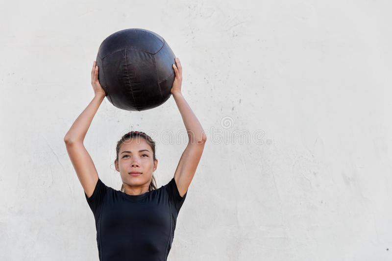 Fitness girl training shoulders with medicine ball. Fitness crossfit girl holding medicine ball above head for shoulder press workout in outdoor crossfit gym royalty free stock image