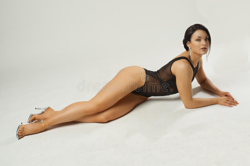 Fitness girl in transparent black bodysuit. It lies in a beautiful pose on a white background stock images