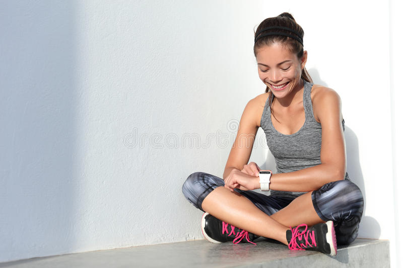 Fitness girl using activity tracker smartwatch as heart rate monitor for workout. Or tracking her weight loss improvement. Woman runner living a healthy life royalty free stock images