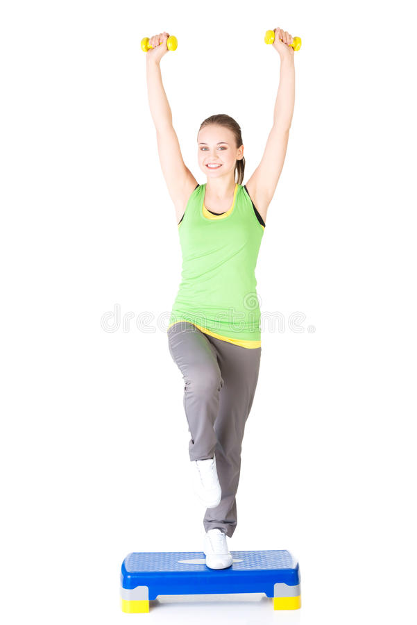 Fitness girl is working out with stepper. Isolated on white background royalty free stock images