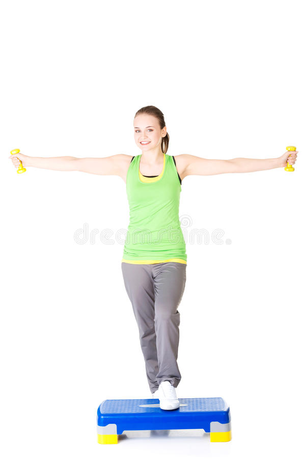 Fitness girl is working out with stepper. Isolated on white background stock images