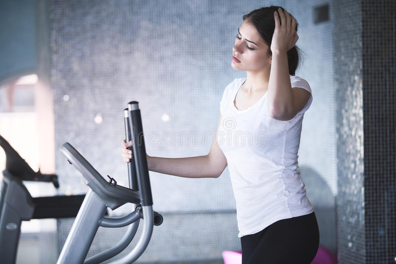 Fitness girl is working out with stepper.Strong brunette with curly hair doing aerobics on stepper. Strong young girl exercising on stepper.Woman doing fitness stock photography