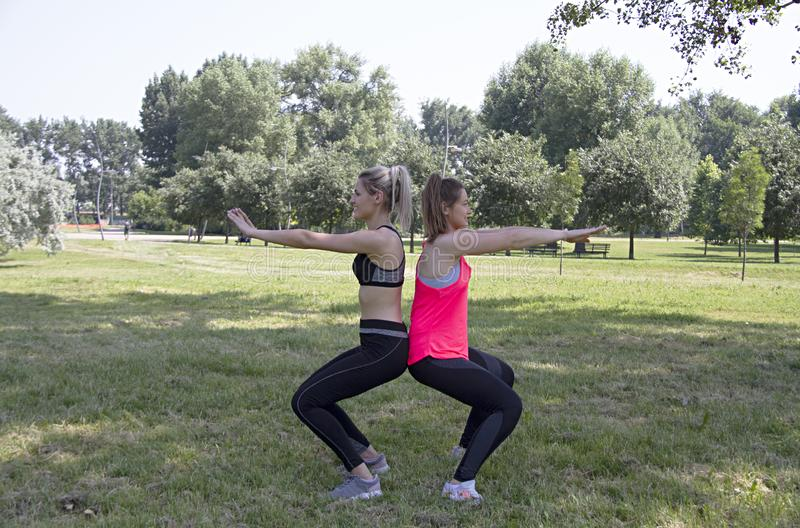 Fitness.The girls work together squats keeping the balance connected with the back of the body. stock images